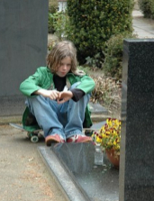child at the grave of a friend